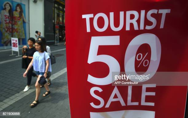 Pedestrians walk past a commercial sign advertising a sale at a shopping district in Seoul on July 25 2017 South Korea's economy is set to grow at...