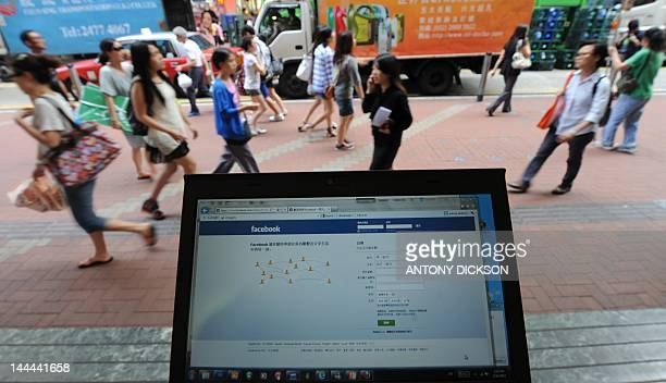 Pedestrians walk past a computer showing the login page for facebook in traditional Chinese characters in Hong Kong on May 14 2012 AFP PHOTO / Antony...