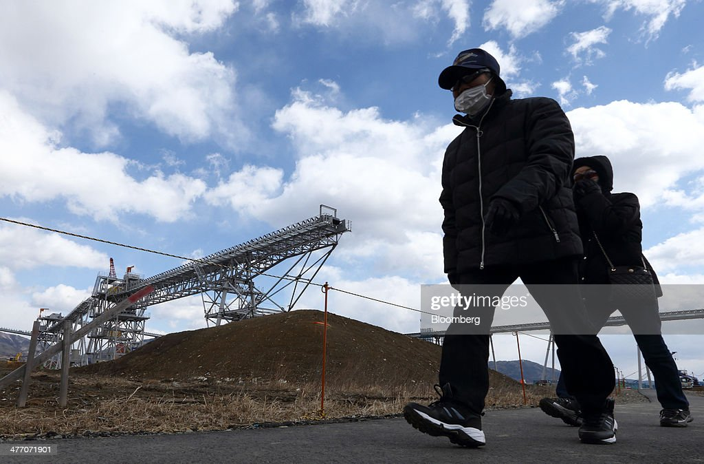 Pedestrians walk past a conveyor carrying excavated soil to a residential area under construction in Rikuzentakata, Iwate Prefecture, Japan, on Thursday, March 6, 2014. Reconstruction of Tohoku, the northern Japan region devastated by the 2011 tsunami, continues as the third anniversary of the disaster approaches. Photographer: Tomohiro Ohsumi/Bloomberg via Getty Images