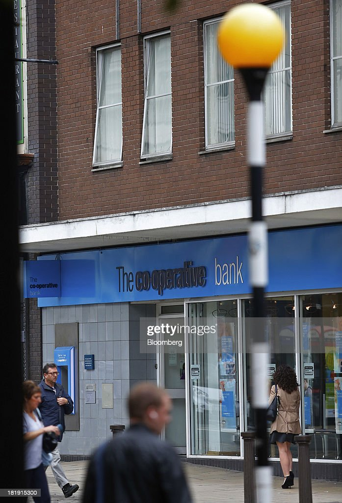 Pedestrians walk past a Co-Operative Bank Plc branch, a unit of Co-Operative Group Ltd., in Bolton, U.K., on Wednesday, Sept. 25, 2013. The parent of Co-operative Bank, which is seeking capital after losses, may avoid being forced to rescue the lender thanks to an accord it struck with regulators last year, according to bondholders. Photographer: Paul Thomas/Bloomberg via Getty Images