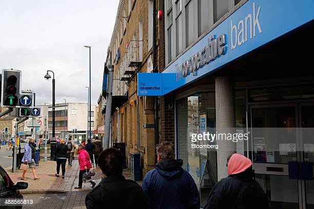 Pedestrians walk past a CoOperative Bank Plc branch in Huddersfield UK on Wednesday May 7 2014 Former CoOperative Bank Chairman Paul Flowers was...