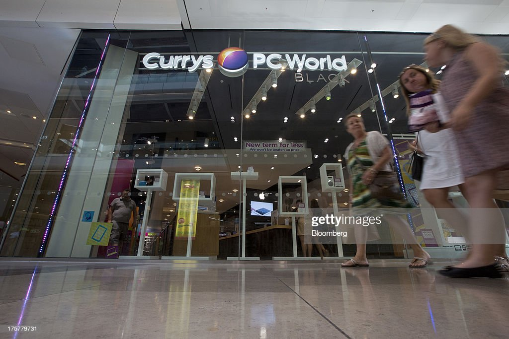 Pedestrians walk past a Currys and PC World 2 in 1 store, operated by Dixons Retail Plc, at the Westfield Stratford City retail complex in London, U.K., on Thursday, Aug. 8, 2013. U.K. consumer confidence rose to the highest in more than three years as Britons' optimism about the economic outlook improved. Photographer: Simon Dawson/Bloomberg via Getty Images