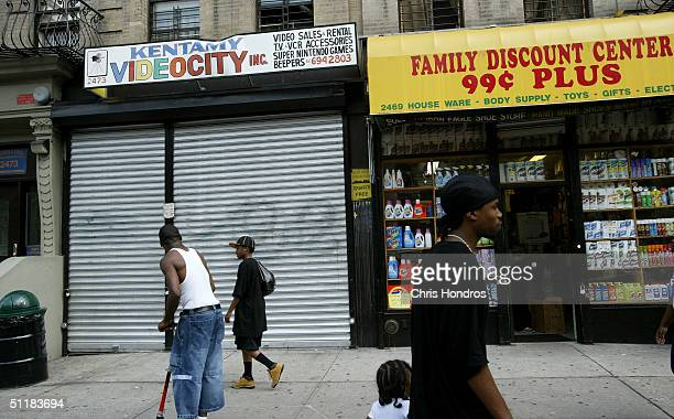 Pedestrians walk past a discount store and a closed shopfront in the Harlem neighborhood August 17 2004 of New York City Over two decades the income...