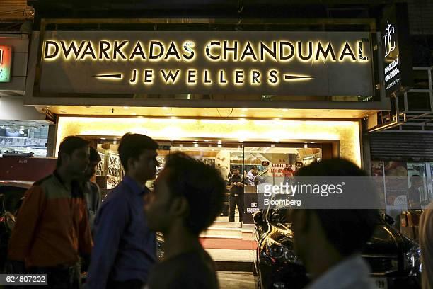 Pedestrians walk past a Dwarkadas Chanduma Jewellers store in Zaveri Bazaar at night in Mumbai India on Friday Nov 18 2016 India's top court refused...