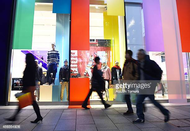 Pedestrians walk past a fashion store on November 21 2014 in Tokyo Japan Japanese Prime Minister Shinzo Abe dissolved the lower house of Parliament...