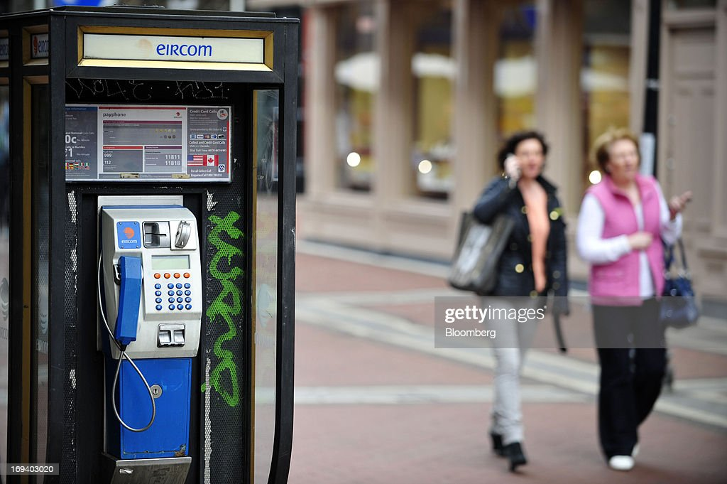 Pedestrians walk past a fixed-line public telephone booth, operated by Eircom Group, in Dublin, Ireland, on Thursday, May 23, 2013. Eircom Group, which has changed ownership six times since 1999, 'would like to be consolidators rather than consolidated' amid expected mergers and acquisitions in the Irish telecoms market, its Chief Financial Officer Richard Moat said. Photographer: Aidan Crawley/Bloomberg via Getty Images
