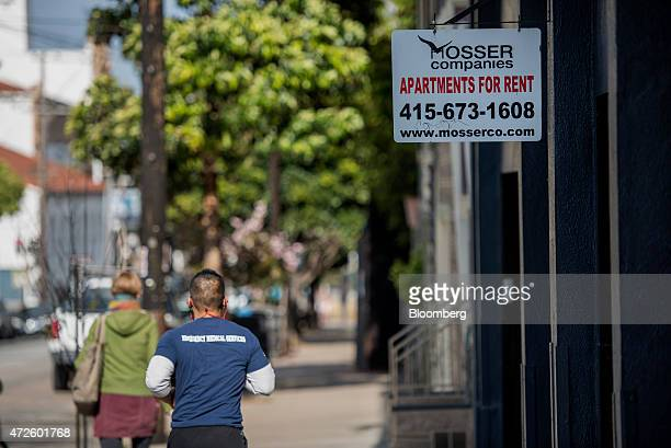 Pedestrians walk past a 'For Rent' sign that is displayed outside of an apartment building in the Mission district of San Francisco California US on...
