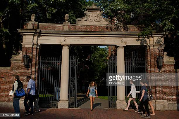 Pedestrians walk past a gate at the Harvard University campus in Cambridge Massachusetts US on Tuesday June 30 2015 Harvard University established in...