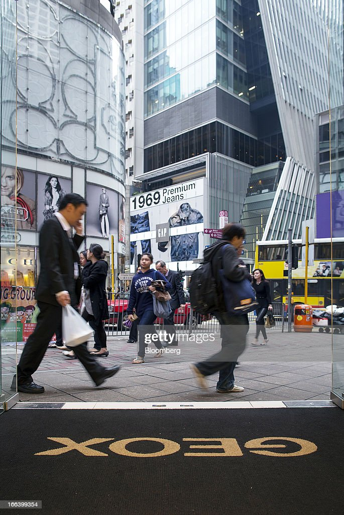 Pedestrians walk past a Geox SpA logo on the doormat of the entrance to the company's flagship store in the Central district of Hong Kong, China, on Friday, April 12, 2013. Hong Kong's economy expanded 1.4 percent in 2012 and Financial Secretary John Tsang is projecting growth of 1.5 percent to 3.5 percent this year. Photographer: Jerome Favre/Bloomberg via Getty Images