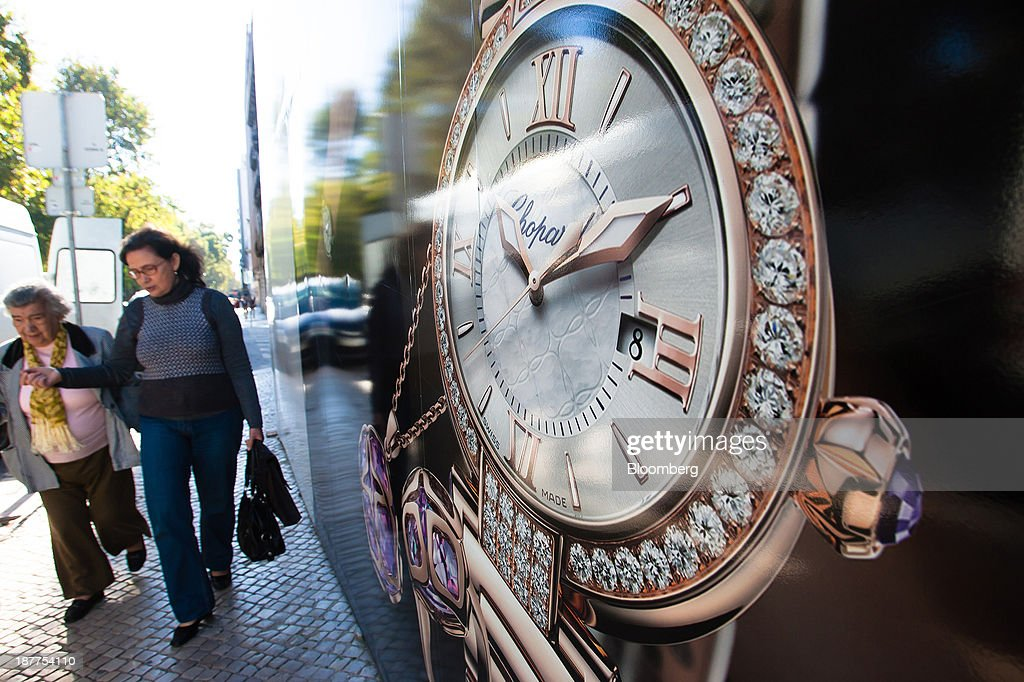 Pedestrians walk past a giant advertisement for Chopard & Cie SA watches on a shopping street in Lisbon, Portugal, on Tuesday, Nov. 12, 2013. Portugal's jobless rate dropped for a second quarter, falling to 15.6 percent in the three months through September as the country's economy shows signs of recovery. Mario Proenca/Bloomberg via Getty Images