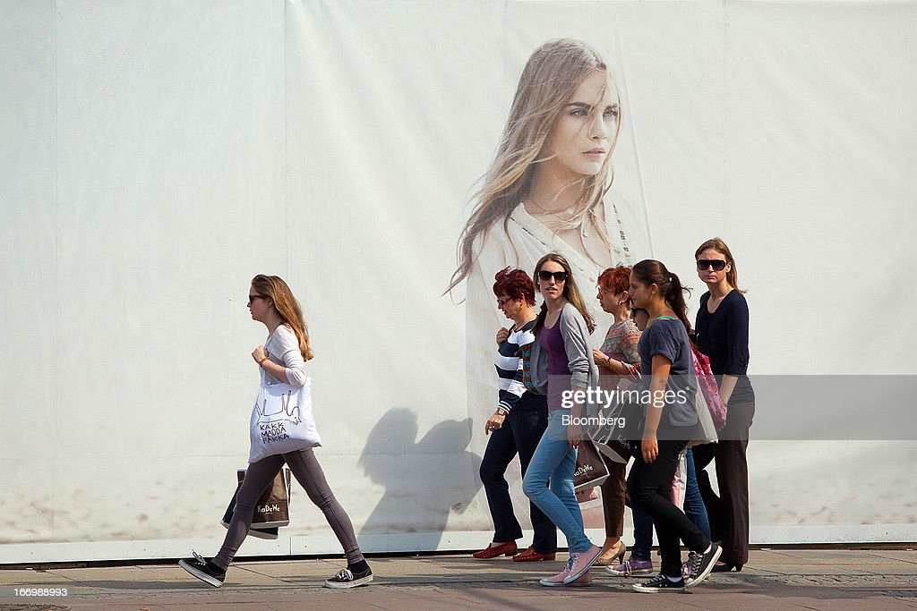 Pedestrians walk past a giant hoarding covering a Zara fashion store, operated by Inditex SA, as it undergoes refurbishment work in Berlin, Germany, on Thursday, April 18, 2013. Germany's economy is shrugging off a contraction at the end of last year and starting to grow due to revived exports and rising private consumption, the country's leading economic institutes said. Photographer: Krisztian Bocsi/Bloomberg via Getty Images
