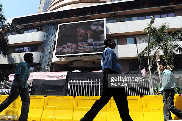 Pedestrians walk past a giant TV screen showing Indian Finance Minister Pranab Mukherjee present the federal budget to parliament on the facade of...