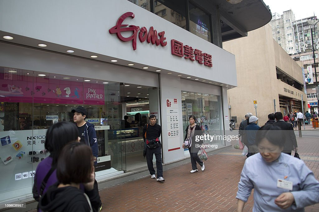 Pedestrians walk past a Gome-branded store in the district of Tsuen Wan in Hong Kong, China, on Monday, Jan. 21, 2012. Gome Electrical Appliances Holding Ltd.'s stocks tumbled in Hong Kong after the company confirmed a report it is closing Gome-branded stores in the city. Photographer: Jerome Favre/Bloomberg via Getty Images