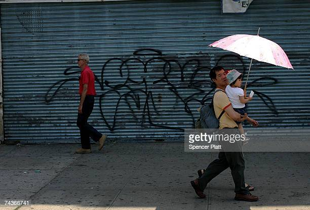 Pedestrians walk past a grafitti strewn wall a May 31 2007 at Coney Island in Brooklyn New York Coney Island has been a summer destination for...
