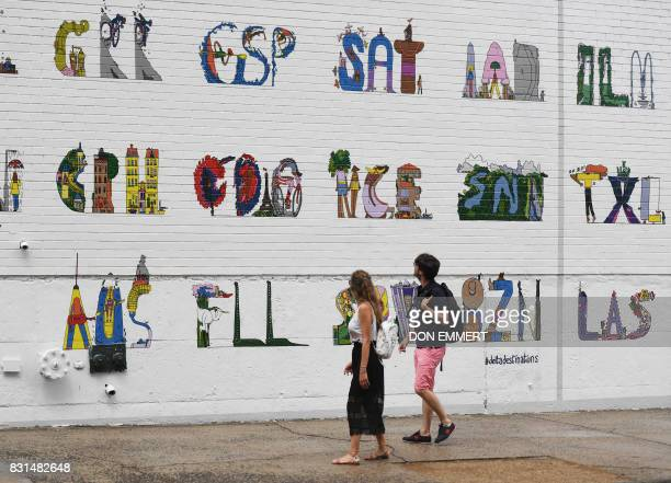 Pedestrians walk past a hand painted ad for Delta Airlines on a building wall August 2 in New York Colossal Media specializes in hand painted ads in...