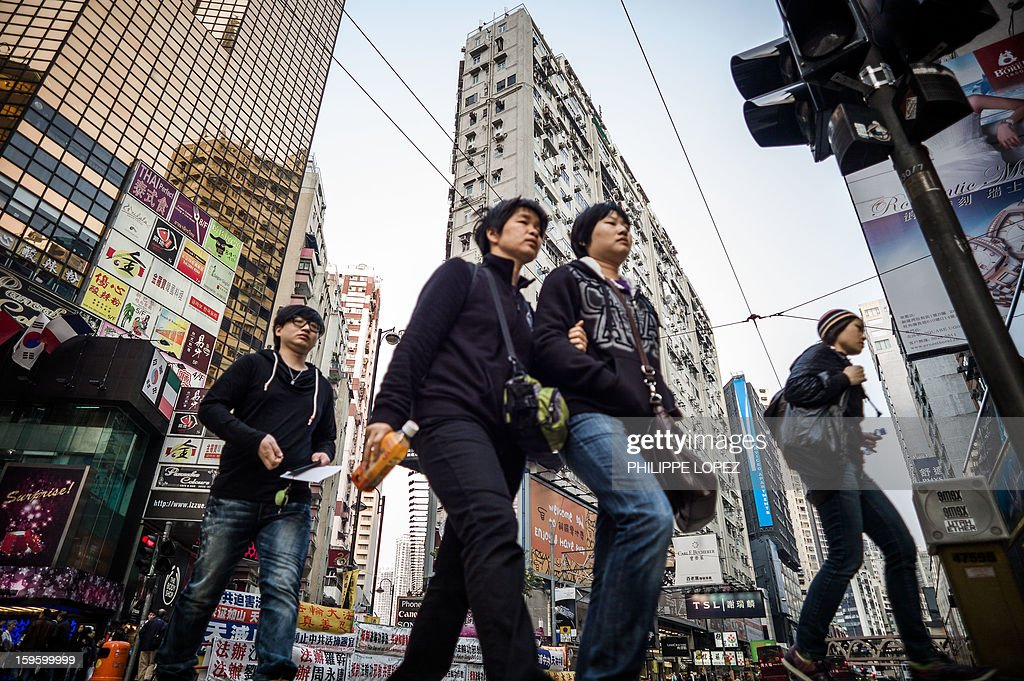 Pedestrians walk past a high rise building in Hong Kong on January 17, 2013. In a January 16, 2013 policy speech aimed at soothing anger following a series of mass protests urging him to quit, Hong Kong Chief Executive Leung Chun-ying said he planned to tackle the city's housing crisis by increasing land supply to provide around 128,700 new homes 'in the short-to medium-term'. AFP PHOTO / Philippe Lopez