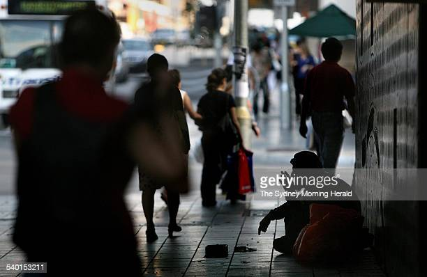 Pedestrians walk past a homeless man begging in the underpass street near Paramatta railway station Sydney 21 November 2006 SMH Picture by KATE...