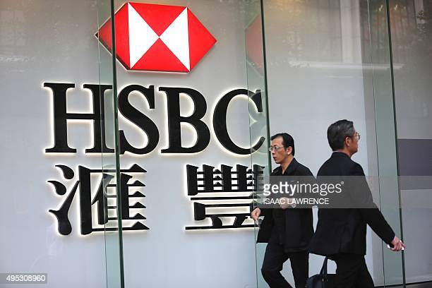 Pedestrians walk past a HSBC sign in Hong Kong on November 2 2015 HSBC saw pretax profit surge 32 percent year on year in the third quarter the...