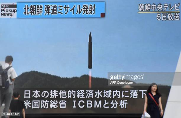 Pedestrians walk past a huge screen in Tokyo on July 29 2017 broadcasting file news footage of North Korean missile launching this month North Korean...