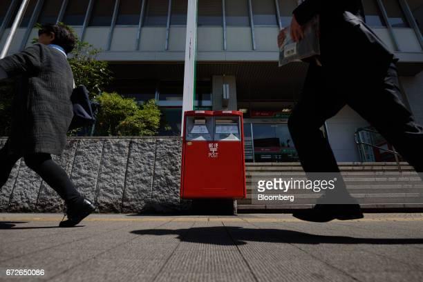 Pedestrians walk past a Japan Post Co mail box in Kawasaki Kanagawa Prefecture Japan on Tuesday April 25 2017 Japan Post Holdings Co Ltdwill book a...