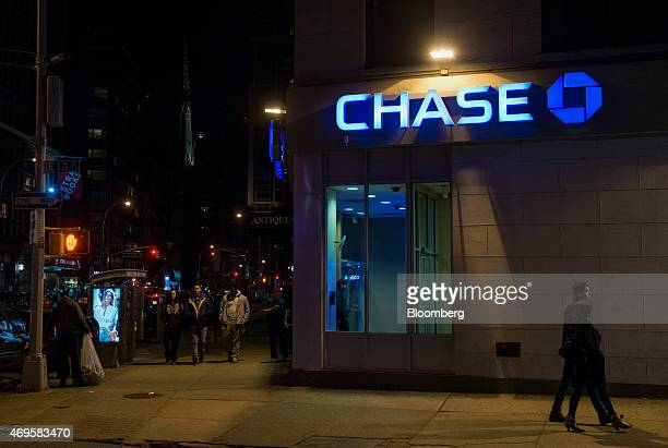 Pedestrians walk past a JPMorgan Chase Co bank branch in New York US on Saturday April 11 2015 JPMorgan Chase Co is scheduled to release earnings...