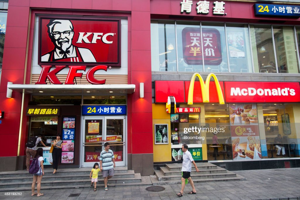 Pedestrians walk past a KFC restaurant, operated by Yum! Brands Inc., left, and a McDonald's Corp. restaurant in the Luohu district of Shenzhen, China, on Monday, Aug. 4, 2014. Yum, owner of KFC and Pizza Hut, said its China team is trying to regain customers after a supply chain scare has recently hurt results. Photographer: Brent Lewin/Bloomberg via Getty Images