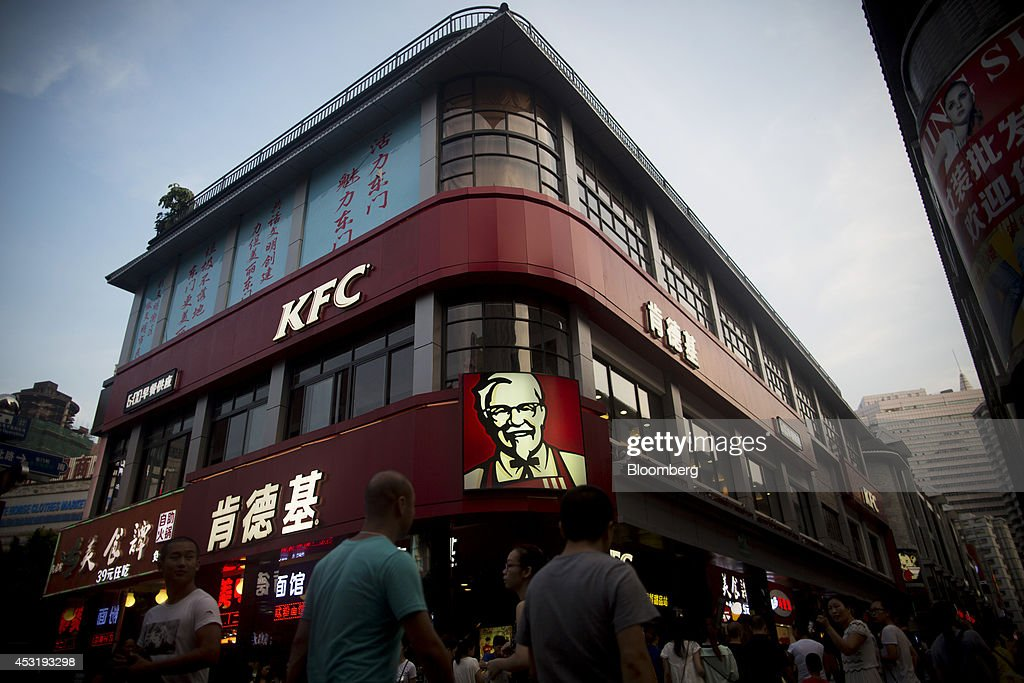 Pedestrians walk past a KFC restaurant, operated by Yum! Brands Inc., in the pedestrianized Dongmen area of Shenzhen, China, on Monday, Aug. 4, 2014. Yum, owner of KFC and Pizza Hut, said its China team is trying to regain customers after a supply chain scare has recently hurt results. Photographer: Brent Lewin/Bloomberg via Getty Images