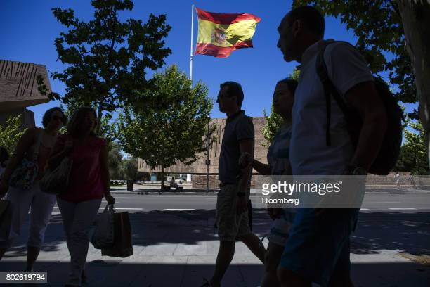Pedestrians walk past a large Spanish national flag flying from a flagpole on Colon Square in Madrid on Wednesday June 28 2017 Bankia SA agreed to...