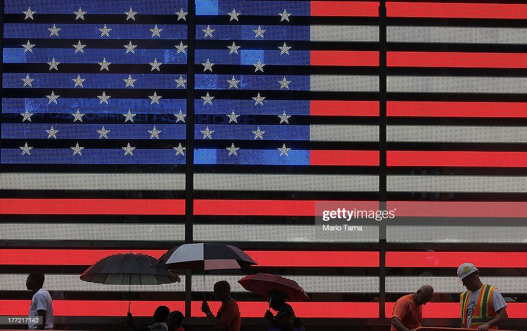 Pedestrians walk past a lighted American flag in the rain in Times Square on August 22, 2013 in New York City. Afternoon rain which fell today in the city is expected to mostly clear by tomorrow.