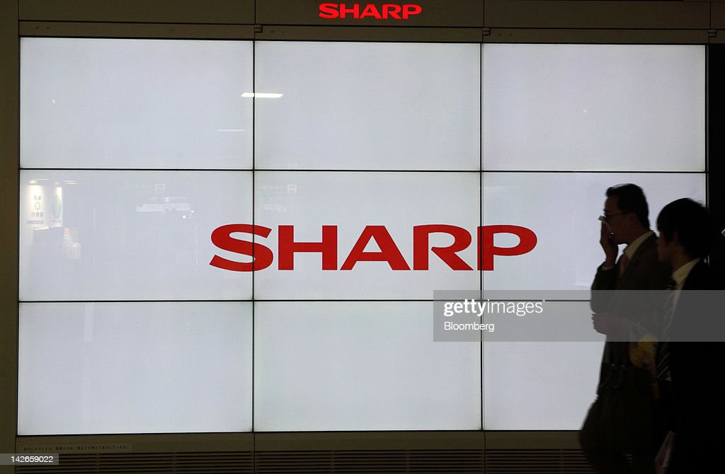 Pedestrians walk past a liquid crystal display (LCD) screen displaying the Sharp Corp. logo in Tokyo, Japan, on Wednesday, April 11, 2012. Sony Corp. and Sharp Corp. posted losses that together equaled 900 billion yen ($11 billion) as the first decline in global TV shipments in six years and a stronger yen eroded earnings at Japan's biggest LCD TV makers. Photographer: Tomohiro Ohsumi/Bloomberg via Getty Images