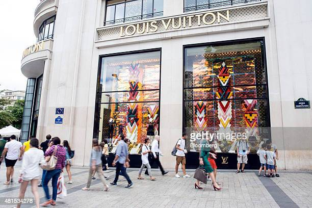 Pedestrians walk past a Louis Vuitton luxury goods store operated by LVMH Moet Hennessy Louis Vuitton SA in Paris France on Tuesday July 21 2015 The...