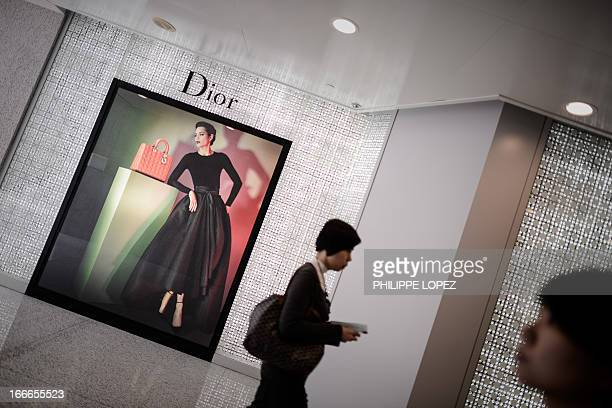 Pedestrians walk past a luxury shop in a shopping mall in Hong Kong on April 15 2013 The Asian financial hub is known for its courting of expensive...