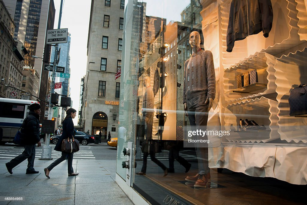 Pedestrians walk past a LVMH Moet Hennessy Louis Vuitton SA store on 5th Avenue in New York US on Tuesday April 8 2014 Consumer Comfort figures are...