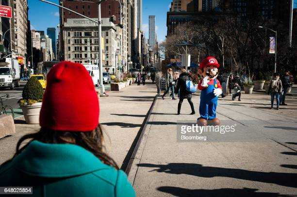 Pedestrians walk past a mascot dressed as Nintendo Co's videogame character Mario outside of the company's launch event in New York US on Friday...