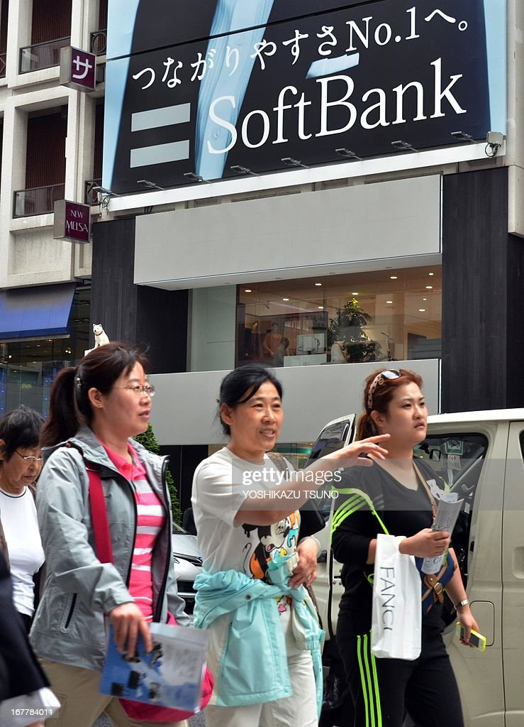 Pedestrians walk past a mobile phone shop of Japan's mobile communication giant Softbank in Tokyo on April 30, 2013. Softbank, which goes ahead with a 20 billion USD takeover of US firm Sprint Nextel, said its annual net profit slipped 7.8 percent on investment-linked losses. Softbank posted a net profit of 289.40 billion yen (2.96 billion USD) on sales of 3.38 trillion yen, up 5.5 percent from a year earlier. AFP PHOTO / Yoshikazu TSUNO