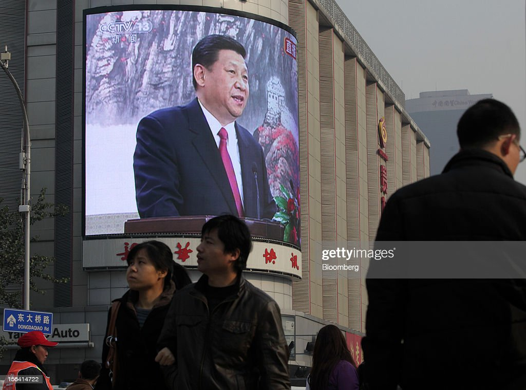 Pedestrians walk past a monitor broadcasting a news conference by Xi Jinping, general secretary of the Communist Party of China, outside a subway station in Beijing, China, on Thursday, Nov. 15, 2012. Xi replaced Hu Jintao as head of the Chinese Communist Party and the nation's military, ushering in the fifth generation of leaders who are set to run the world's second-biggest economy over the next decade. Photographer: Tomohiro Ohsumi/Bloomberg via Getty Images