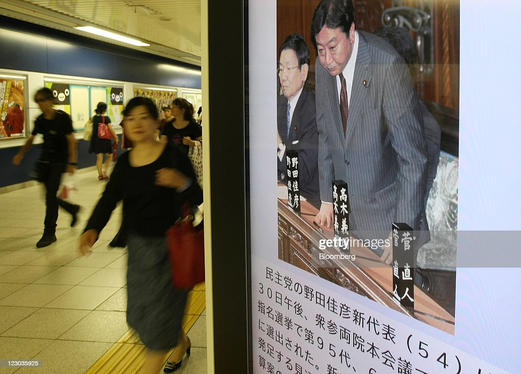 Pedestrians walk past a monitor displaying a news report on Yoshihiko Noda, president of the Democratic Party of Japan (DPJ) and Japan's newly named prime minister, at a train station in Tokyo, Japan, on Tuesday, Aug. 30, 2011. Noda becomes Japan's sixth leader in five years, seeking a consensus to raise taxes to pay for rebuilding from the March earthquake and nuclear disaster and reduce the world's largest debt. Photographer: Tomohiro Ohsumi/Bloomberg via Getty Images