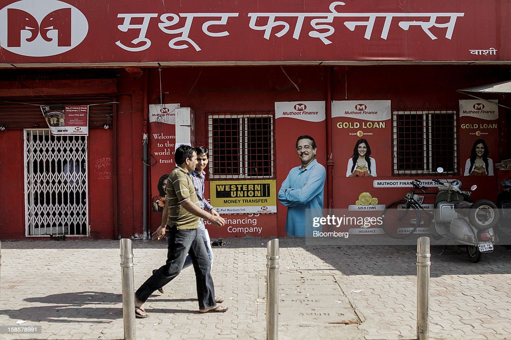 Pedestrians walk past a Muthoot Finance Ltd. branch in Mumbai, India, on Tuesday, Dec. 18, 2012. Muthoot Finance Ltd. is India's biggest lender that uses gold jewelry as collateral. Photographer: Dhiraj Singh/Bloomberg via Getty Images