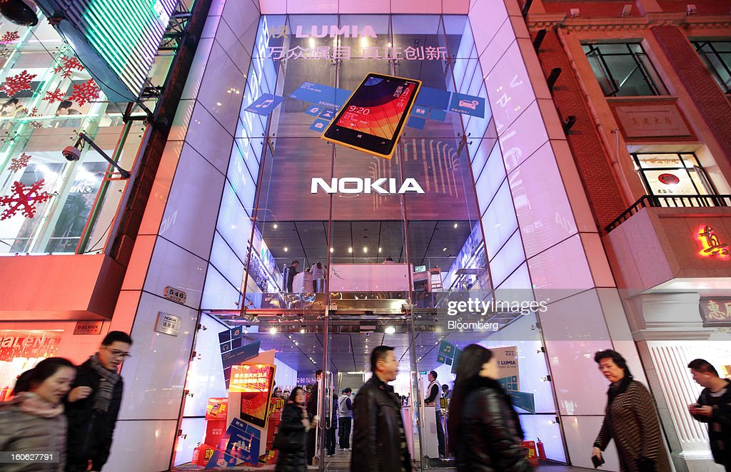 Pedestrians walk past a Nokia Oyj store at night in the East Nanjing Road shopping area of Shanghai, China, on Friday, Feb. 1, 2013. China's services industries grew at the fastest pace since August as gains in retailing and construction aid government efforts to drive a recovery in the world's second-biggest economy. Photographer: Tomohiro Ohsumi/Bloomberg via Getty Images