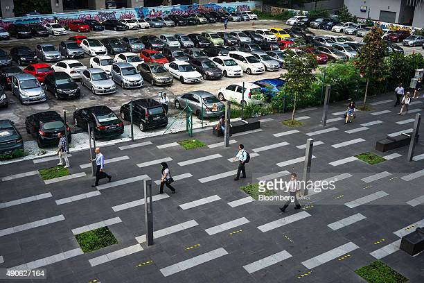 Pedestrians walk past a parking lot in the central business district of Kuala Lumpur Malaysia on Tuesday Sept 29 2015 The ringgit's weakness slowing...