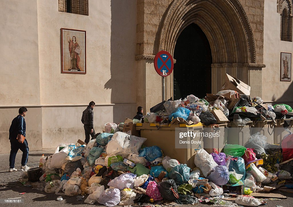 Pedestrians walk past a pile of uncollected grabage during the 11th day of the waste disposal strike on February 7, 2013 in Seville, Spain. Waste disposal workers are striking over a 5% proposed cut in their salary and an extended working week to 37.5 hours.