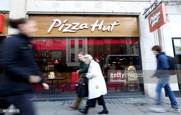 Pedestrians walk past a Pizza Hut restaurant owned by Yum Brands Inc on The Strand in London UK on Tuesday March 24 2015 Pizza Hut owned by...
