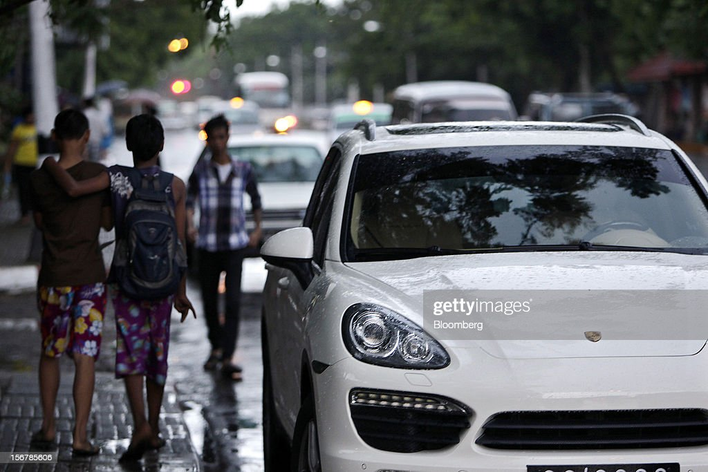 Pedestrians walk past a Porsche SE Cayenne vehicle parked by the side of the road in Yangon, Myanmar, on Tuesday, Nov. 20, 2012. Myanmar's growth outlook has improved 'substantially' amid political reforms, which are expected to lead to a large influx of foreign investment, the Organization for Economic Cooperation and Development (OECD) said on Nov. 18. Photographer: Dario Pignatelli/Bloomberg via Getty Images