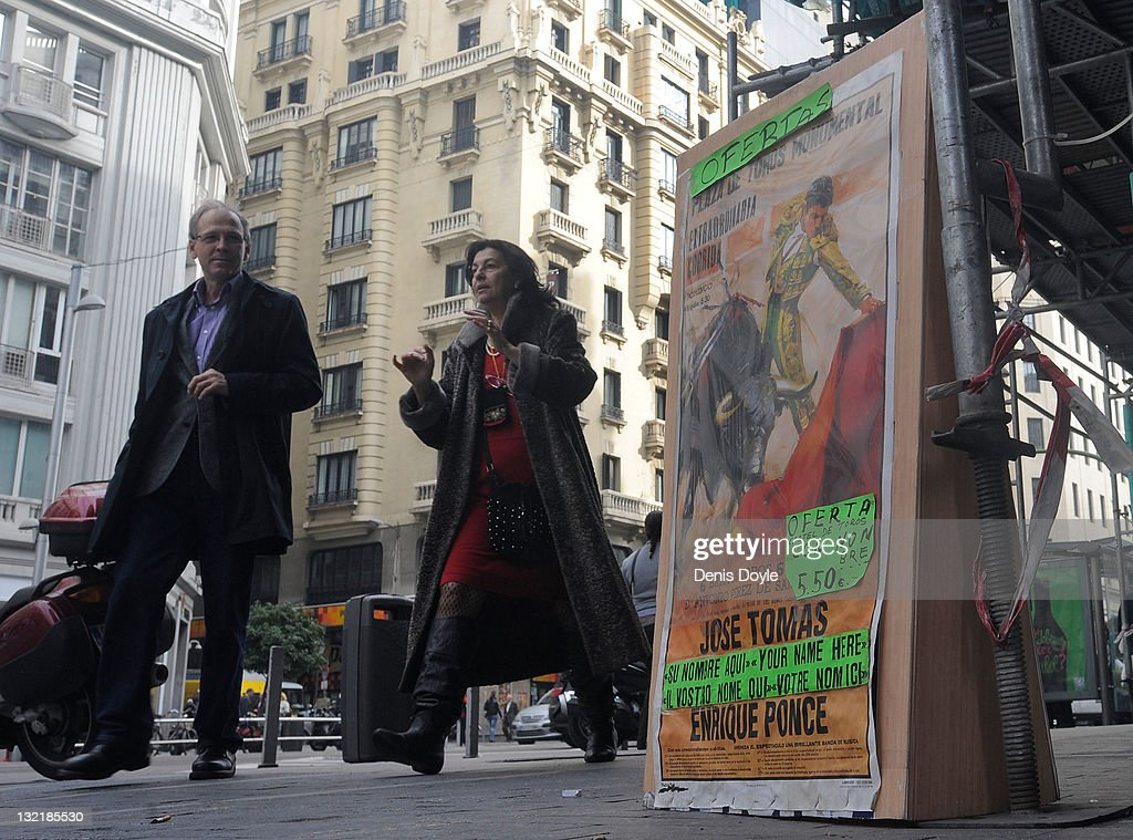 Pedestrians walk past a poster of Spanish bullfighter Jose Tomas on Calle Gran Via on November 10, 2011 in Madrid, Spain. The current Eurozone debt crisis has left Spain with crippling economic problems. Mounting debts, record unemployment figures and the recent credit rating downgrade is leaving the country facing further economic stagnation. The people of Spain are preparing to go to the polls for a general election which will be held on November 20, 2011