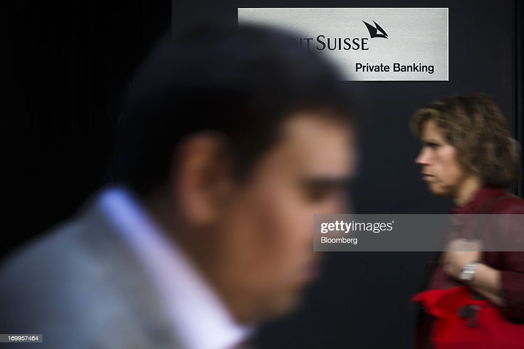 Pedestrians walk past a private banking sign for Credit Suisse Group AG in Geneva, Switzerland, on Wednesday, June 5, 2013. Members of the Swiss parliament's upper house's economic committee have been debating a law which, if passed, could authorize Swiss banks to cooperate with U.S. authorities. Photographer: Valentin Flauraud/Bloomberg via Getty Images