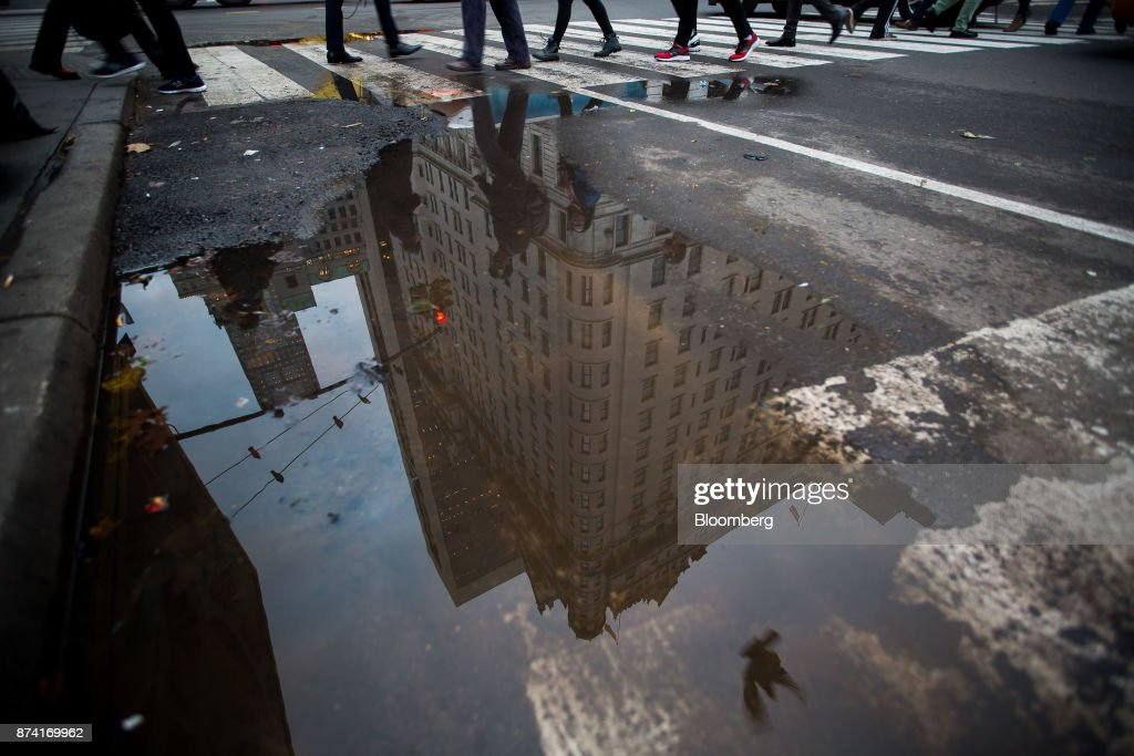 Pedestrians walk past a puddle reflecting the Plaza Hotel in New York, U.S., on Monday, Nov. 13, 2017. Billionaire Saudi Prince Alwaleed bin Talal has long been associated with New York's iconic Plaza Hotel, ever since he bought out Donald Trump over two decades ago. Photographer: Michael Nagle/Bloomberg via Getty Images