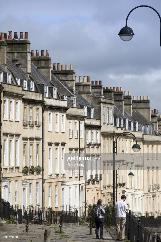Pedestrians walk past a row of terraced houses on a suburban street in Bath, U.K. on Monday, Aug. 21, 2017. U.K. property prices stagnated in July as a slump in London values spread to neighboring areas, according to theRoyal Institution of Chartered Surveyors. Photographer: Jason Alden/Bloomberg via Getty Images