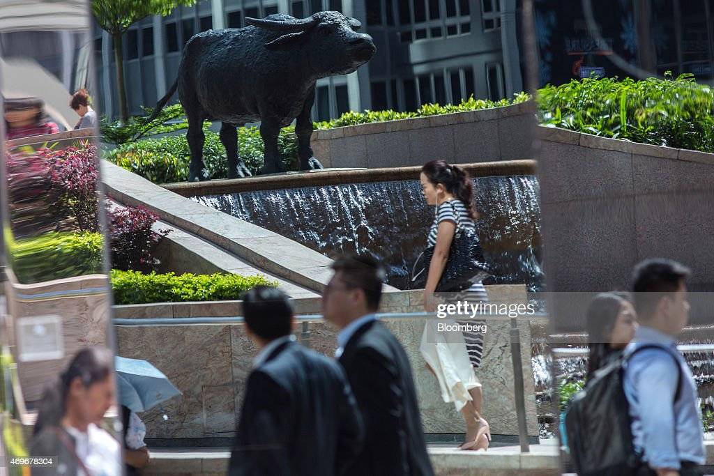 Pedestrians walk past a sculpture of a water buffalo in a plaza at Exchange Square in Hong Kong China on Tuesday April 14 2015 Chinese stocks trading...