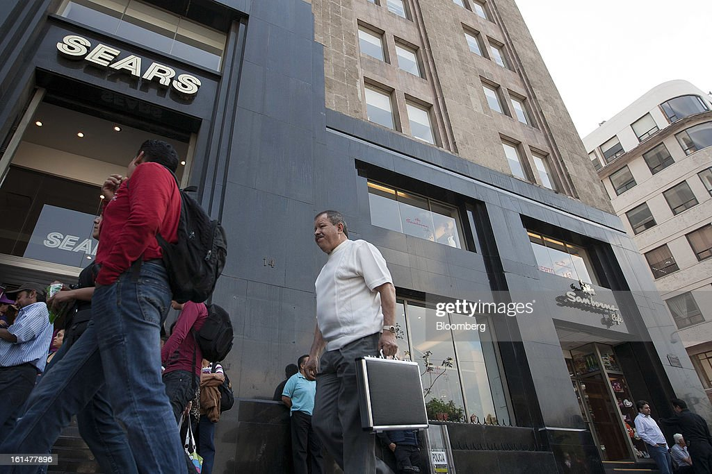 Pedestrians walk past a Sears and a Grupo Sanborns SAB store in Mexico City, Mexico, on Friday, Feb. 8, 2013. Grupo Sanborns SAB, the retailer controlled by Mexican billionaire Carlos Slim, raised 10.5 billion pesos ($825 million) in an initial public offering (IPO) last week and the total could climb to 12.1 billion pesos including an overallotment option for underwriters. Photographer: Susana Gonzalez/Bloomberg via Getty Images