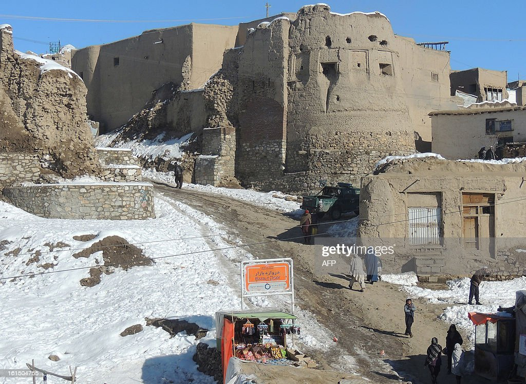 Pedestrians walk past a section of the old city as snow is pictured on the ground in Ghazni province on February 12, 2013. Ghazni, located in eastern Afghanistan along the Kabul-Kandahar road, is one of the thirty-four provinces and one of Afghanistan's major cities with an estimated population of 141,000 people. AFP PHOTO/ Rahmatullah Alizad